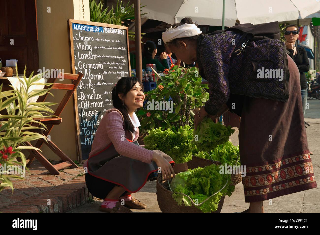 Junge Frau kaufen Salat von ältere Dame für ein Restaurant, Luang Prabang, Laos Stockbild
