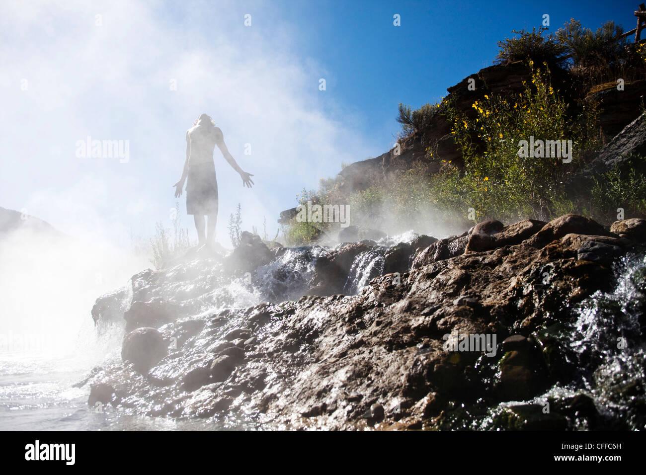 ein junger Mann stehend in einer Bank von Dampf in einem Hotspring in Montana. Stockbild