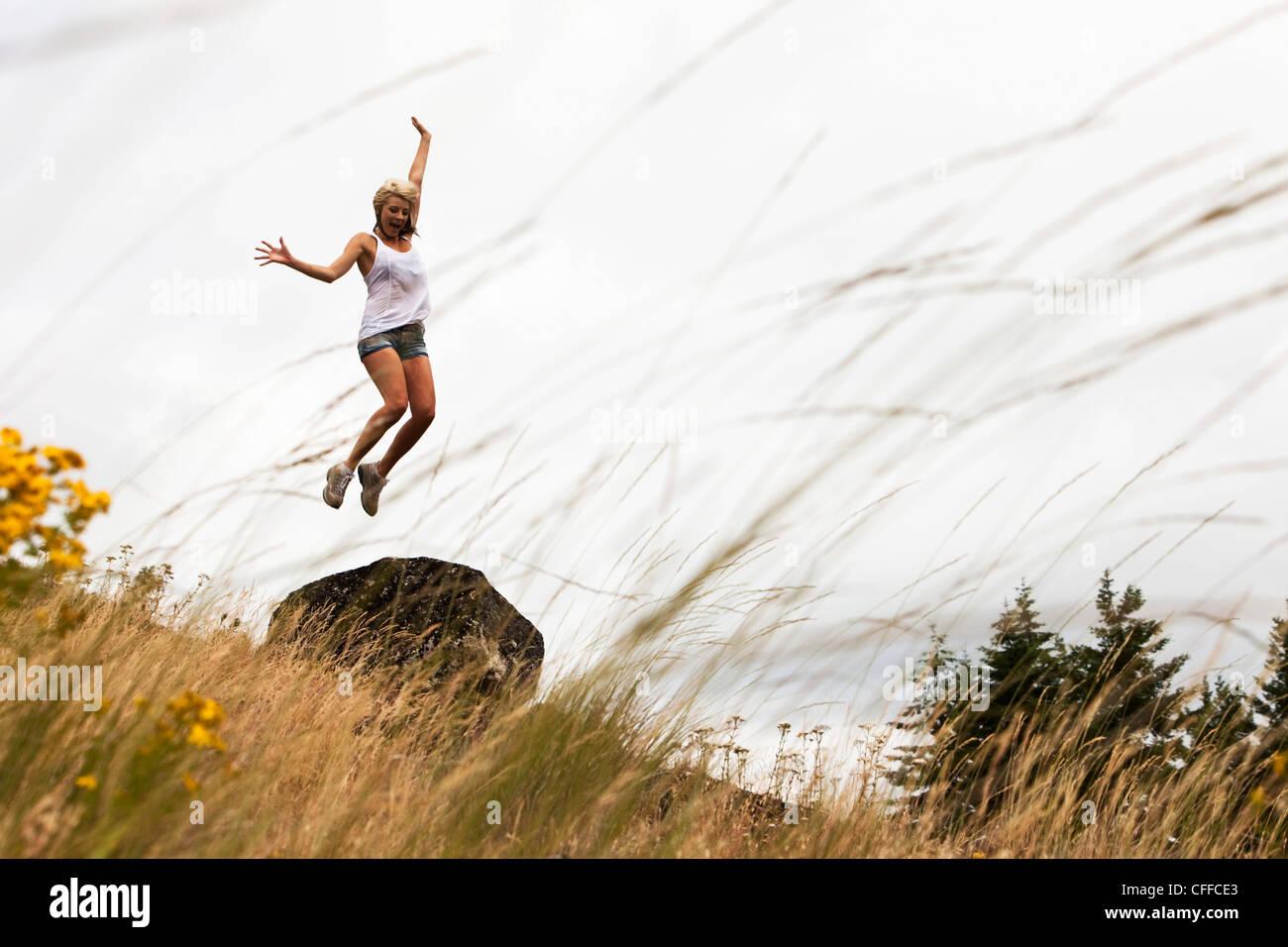 Eine junge Frau springt in die Luft in Idaho. Stockbild