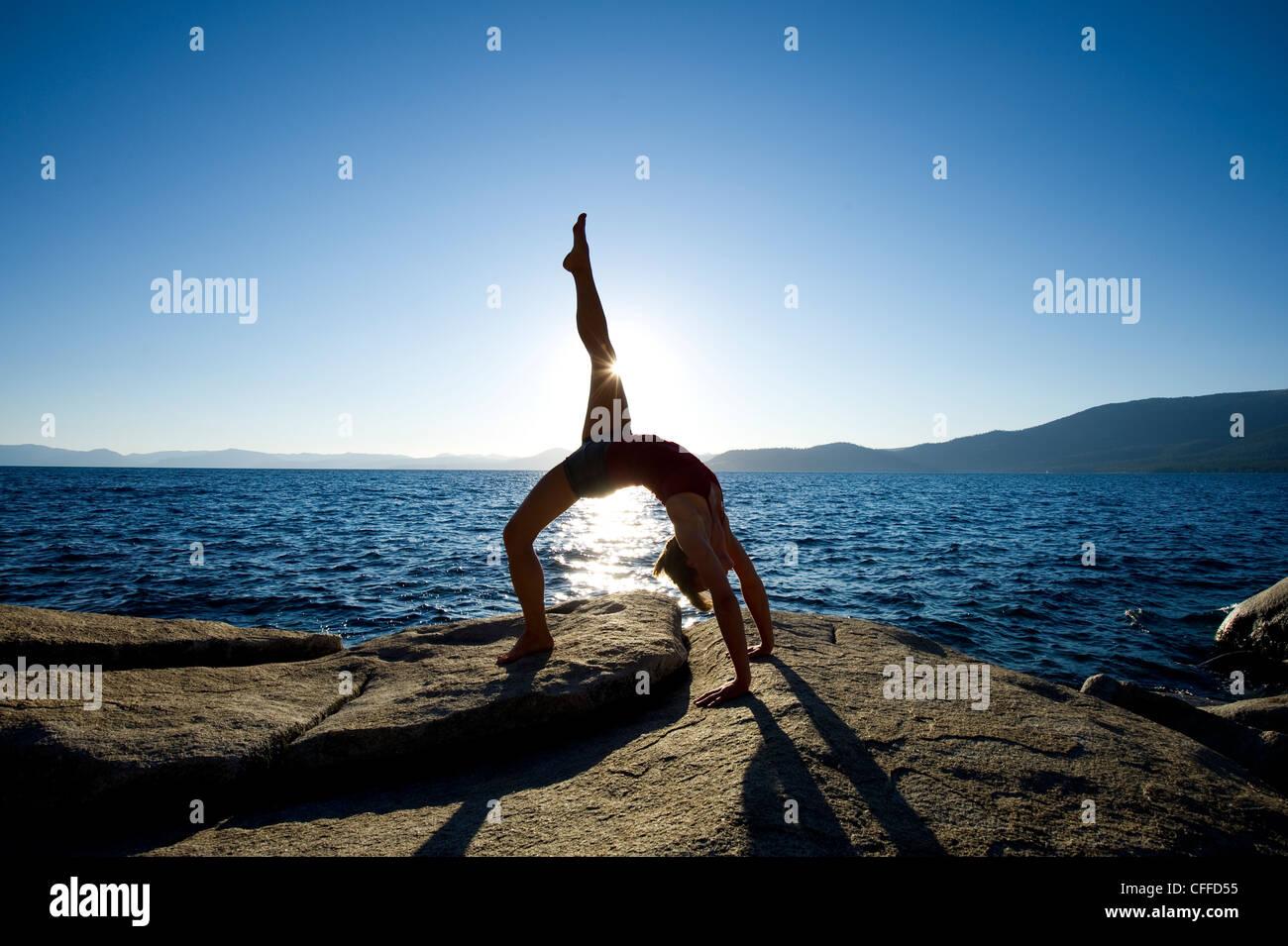 Eine Silhouette einer jungen Frau, die Durchführung von Yoga auf einem Granitblock am Ostufer des Lake Tahoe, Stockbild