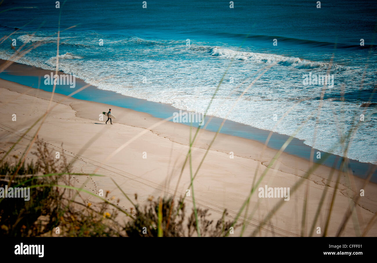 Eine Surfer geht einen Strand. Stockbild