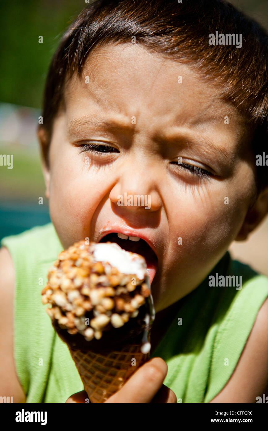 Ein kleiner Junge isst ein Eis an einem Straßenrand Gemischtwarenladen in den Bergen von Colorado. Stockbild