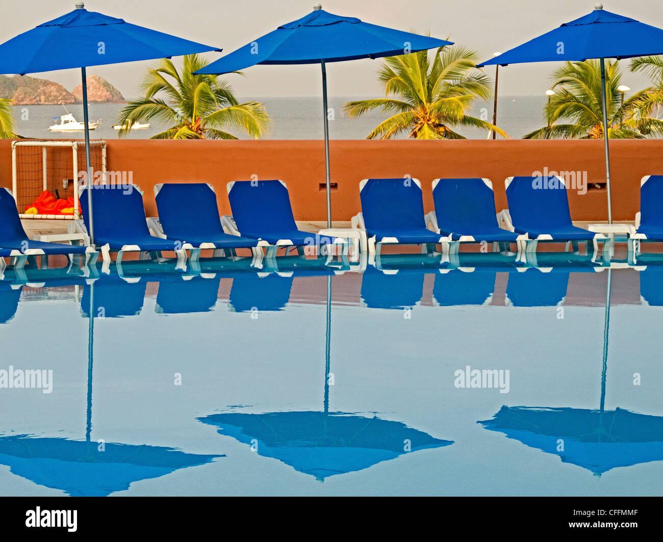 Blaue Sonnenliegen und Sonnenschirmen und ihre Reflexion im Schwimmbad Melia Azul Ixtapa in Ixtapa/Zihuatanejo, Stockbild