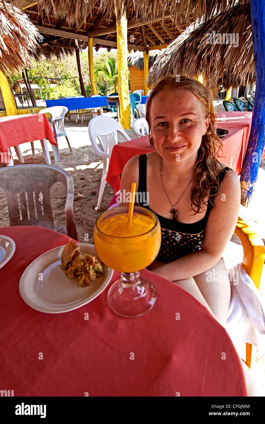 Eine junge, blonde Frau unter einem Sonnenschirm am Strand von La Isla de Ixtapa/Zihuatanejo, mit einem orange-farbigen Stockbild