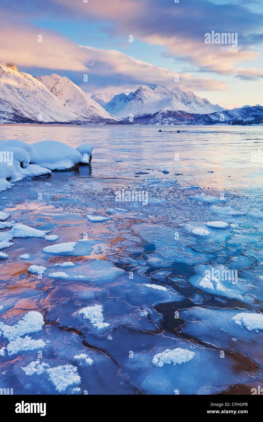Blick über das gefrorene Meer Ullsfjord aus Sjursnes, in Richtung der südlichen Lyngen-Alpen, bei Sonnenuntergang, Stockbild