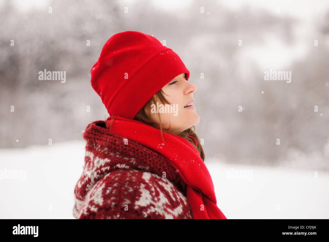 Schöne junge Mädchen mit roter Mütze und Schal genießen den fallenden Winterschnee Stockbild