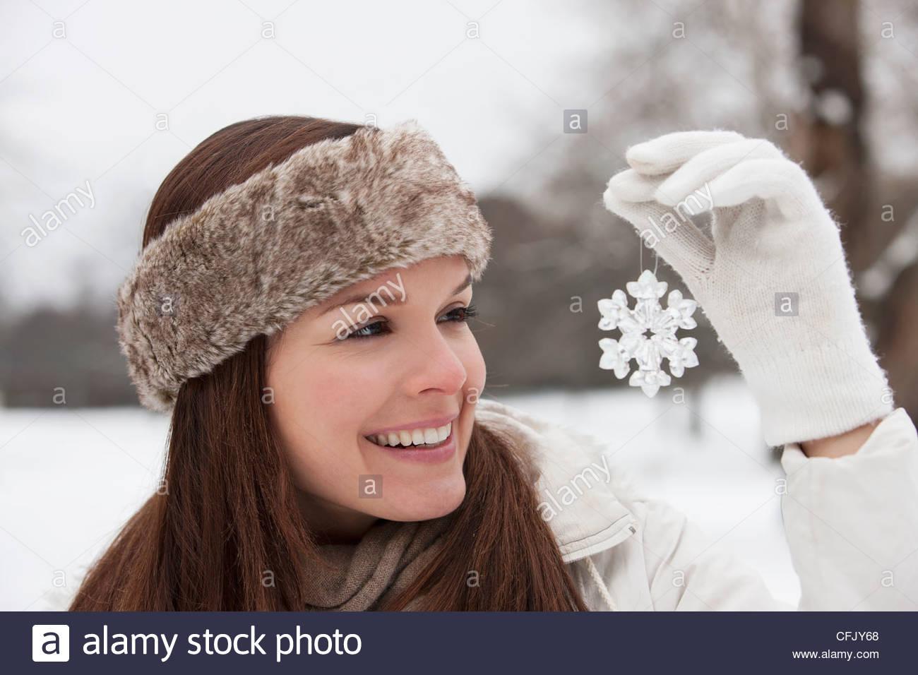 Eine junge Frau hält eine Schneeflocke-Dekoration Stockbild