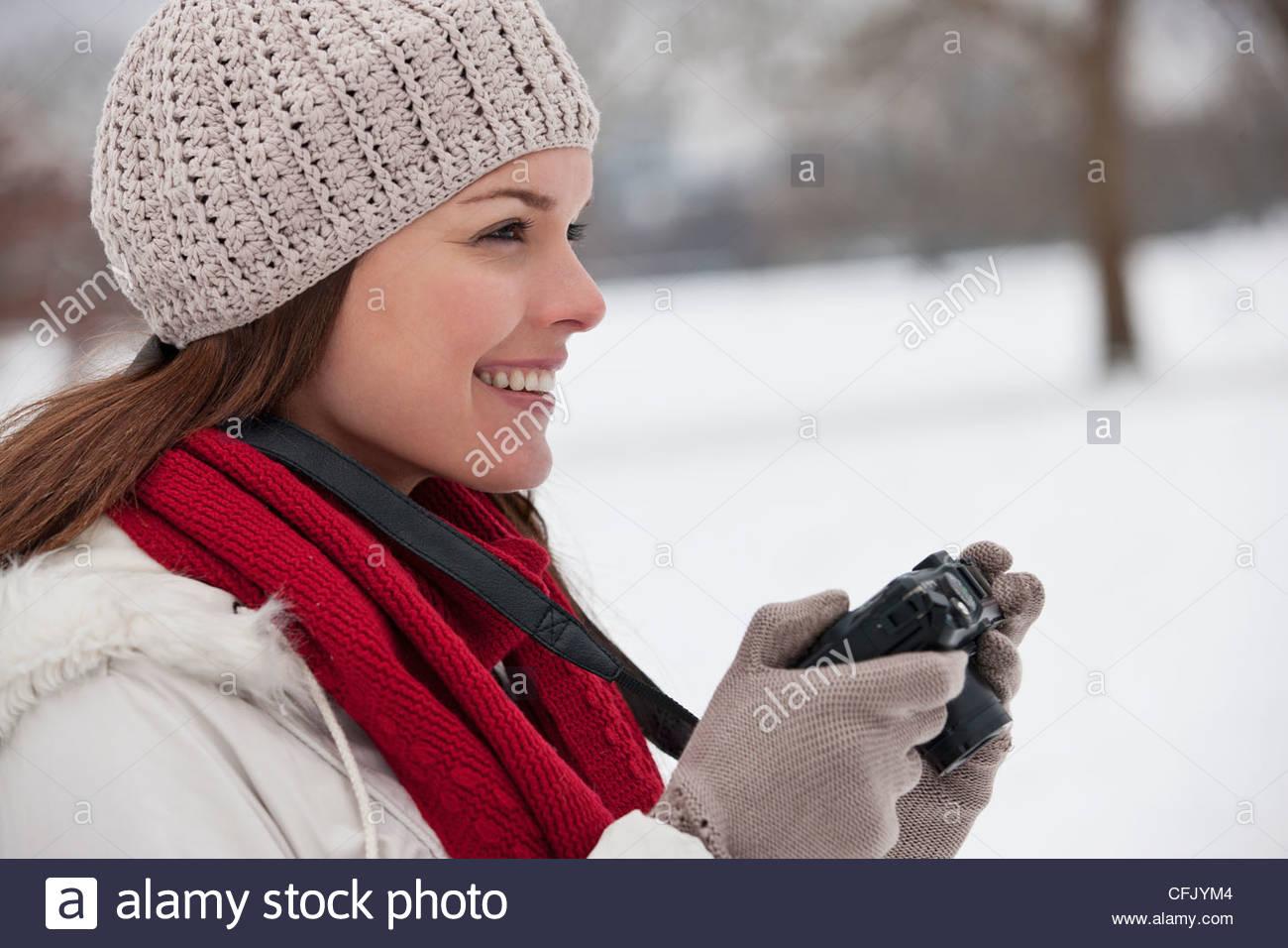 Eine junge Frau im Schnee stehen, eine Kamera zu halten Stockbild