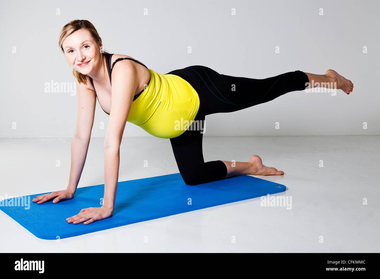 Schwangere Frau auf Matte trainieren Balance und Muskelkraft der ...