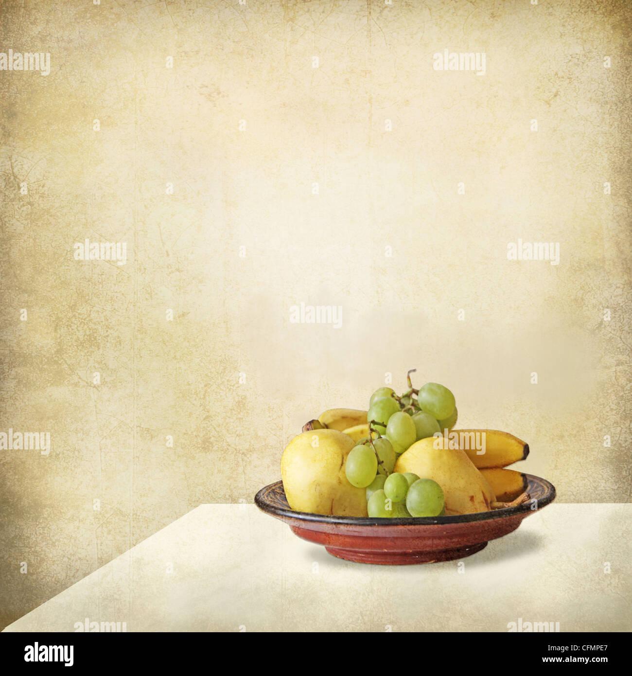 Grunge Stillleben mit einem hellen Interieur, ein Tisch und ein Tablett voller Früchte, Trauben, Bananen, Birnen. Stockfoto
