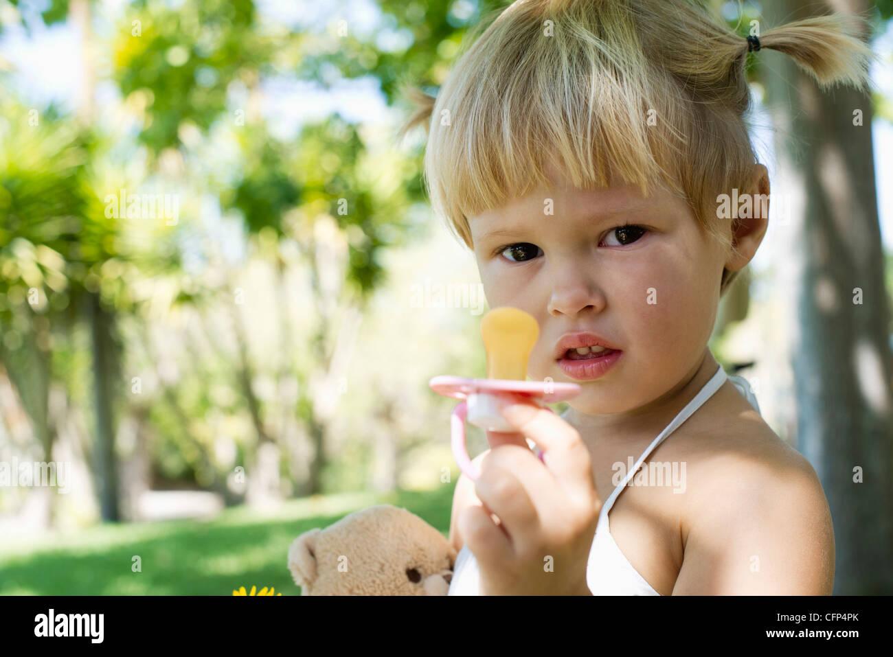 Kleine Mädchen halten Schnuller Stockbild
