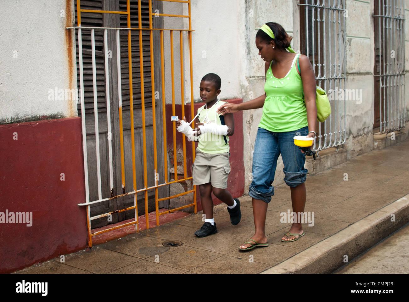 Mutter und San auf der Straße laufen, junge hat beide Arme
