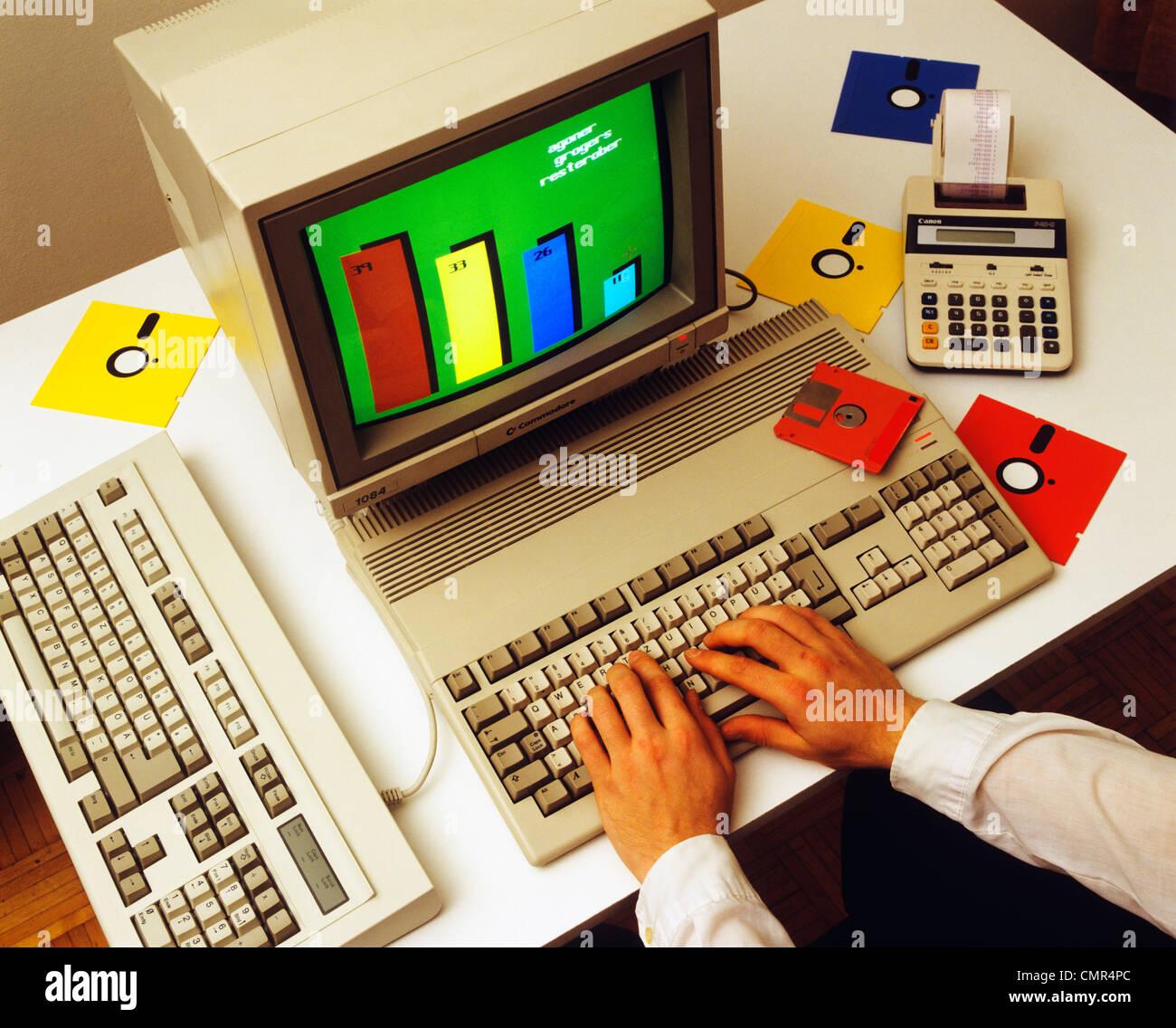 1980ER JAHRE MÄNNLICHE HÄNDE AUF COMPUTER-TASTATUR MIT MONITOR-DISKETTEN-RECHNER Stockbild