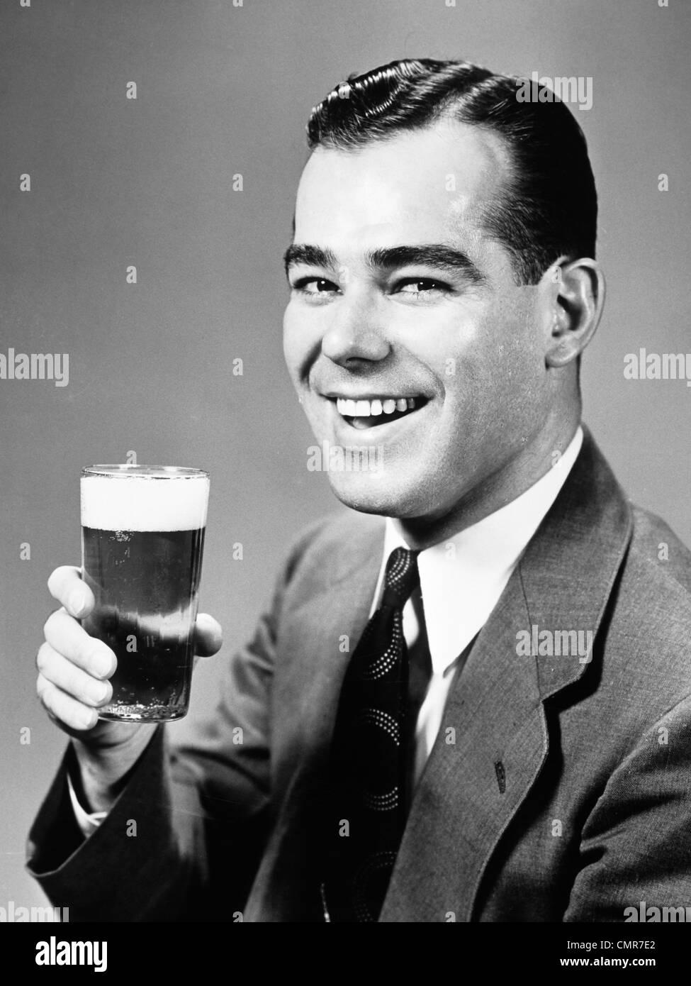 1940ER JAHREN LÄCHELND MANN HOLDING GLAS BIER Stockbild