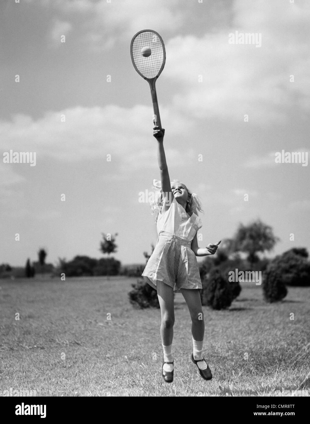 1930ER JAHREN MÄDCHEN SPIELEN TENNIS SPRINGEN, UM DEN BALL ÜBER KOPF ZU SCHLAGEN Stockbild