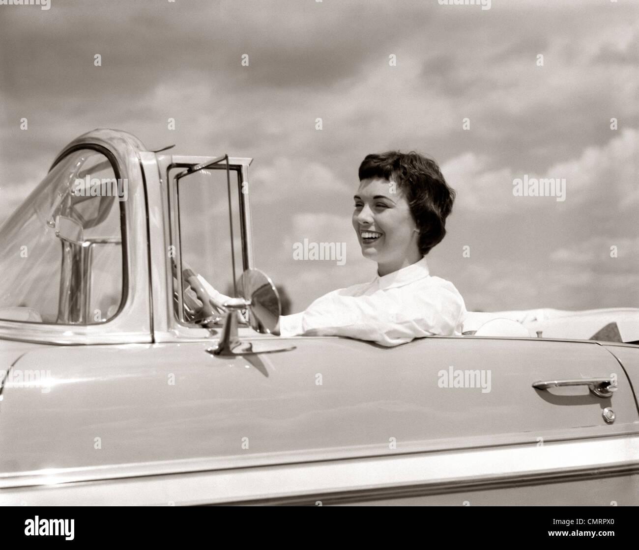 1950ER JAHREN LÄCHELNDE FRAU FAHREN CHEVROLET CABRIO AUTO Stockbild