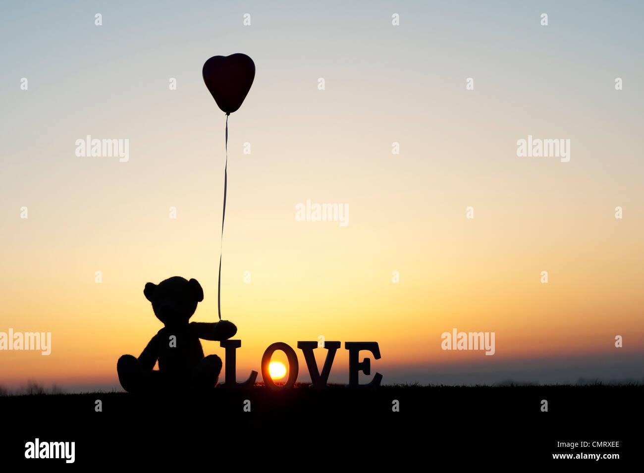 Teddy Bär hält ein Herzballon Form als nächstes auch das Wort Liebe bei Sonnenaufgang Stockbild