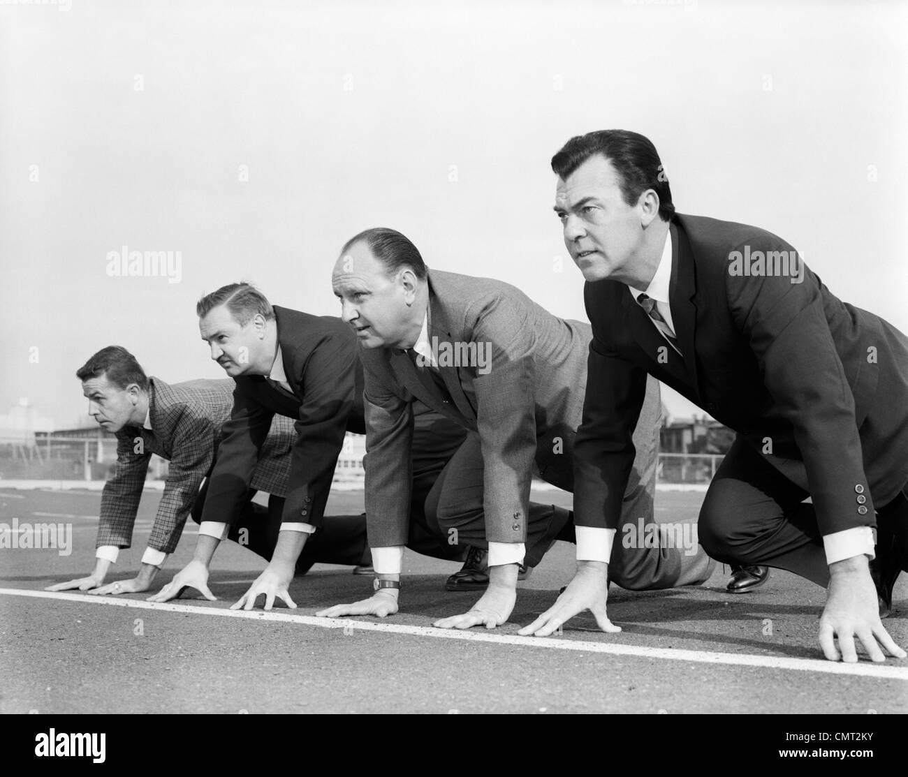 1960ER JAHREN VIER GESCHÄFTSLEUTEN AUF DER STARTLINIE Stockbild