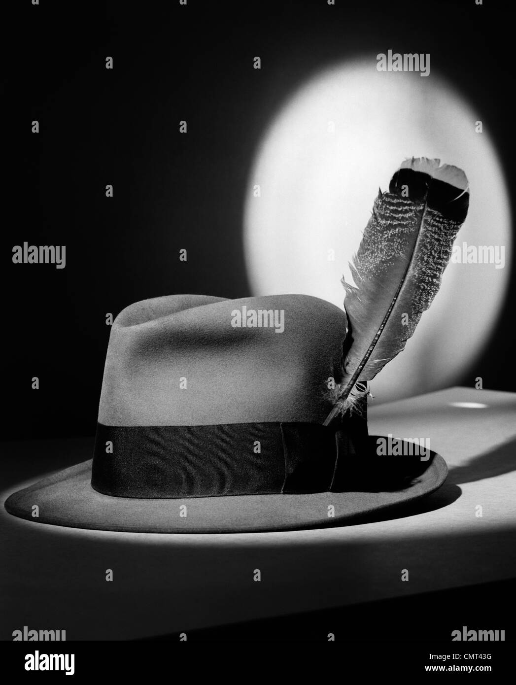 1940ER JAHRE FILZHUT MIT FEDER IN BAND IN SPOTLIGHT SYMBOLISCHE FEDER IN DER KAPPE Stockbild