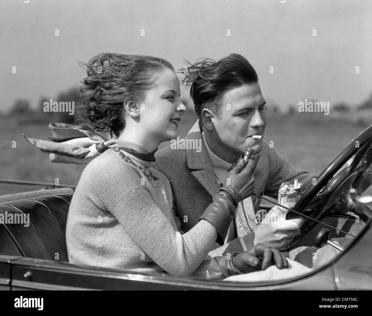 1930ER JAHRE MANN CABRIO AUTO FAHREN, WÄHREND FREUNDIN SEINE ZIGARETTE LEUCHTET Stockbild
