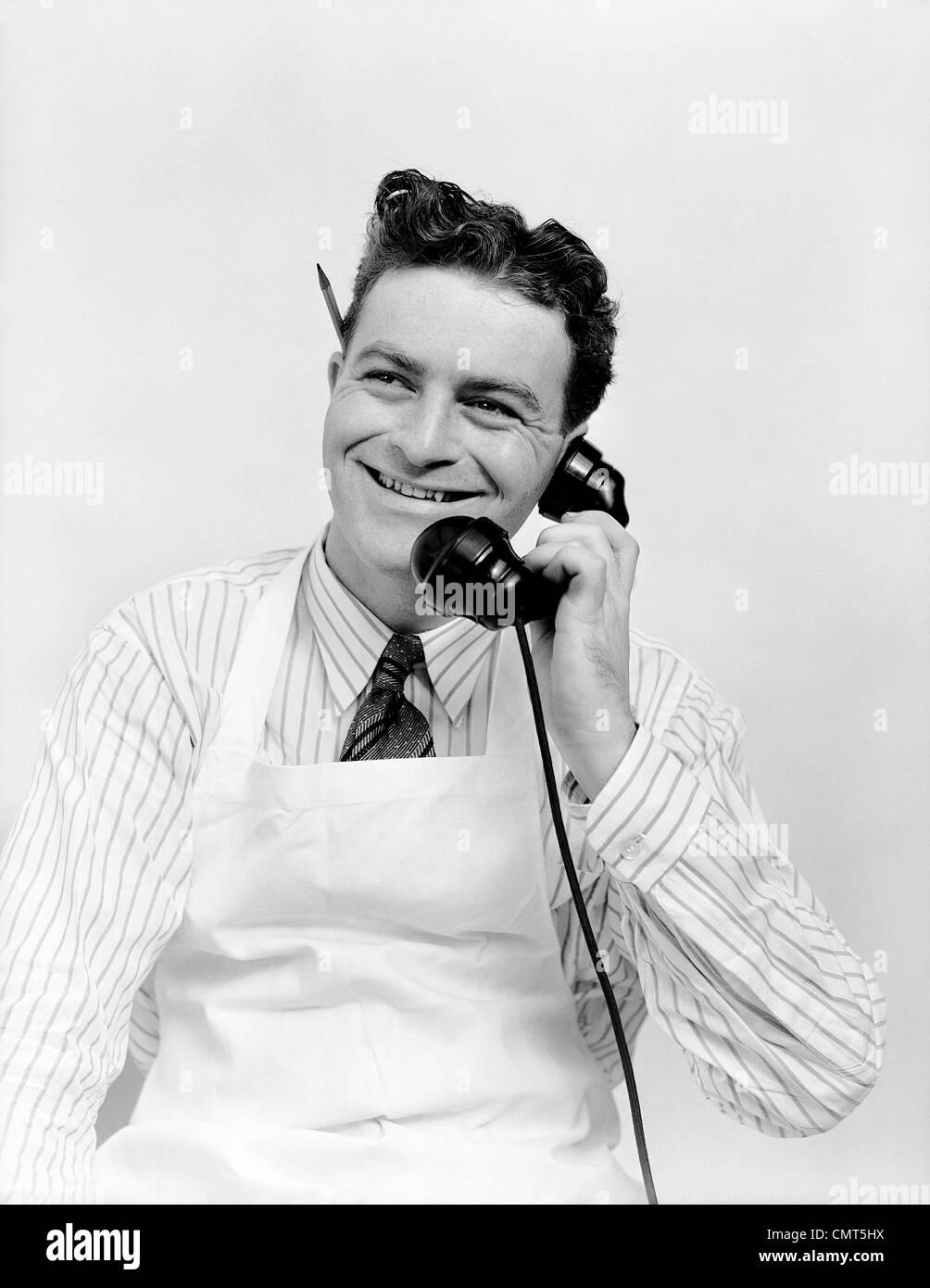 1930ER JAHRE PORTRAIT LÄCHELND MANN SCHREIBER TRÄGT SCHÜRZE GESPRÄCH AM TELEFON BLEISTIFT HINTER Stockbild
