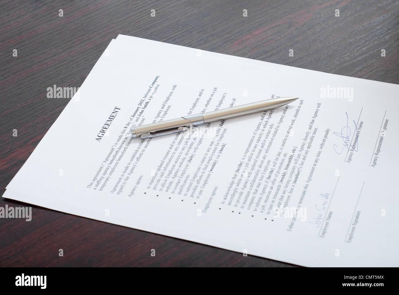 Vertrag mit Silberstift auf dem Tisch Stockbild