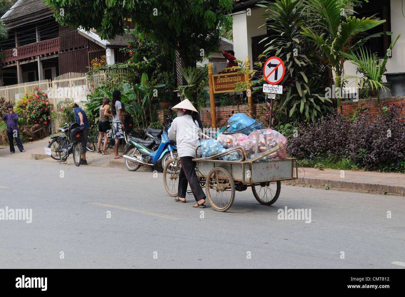 Lao Frau mit einem Fahrrad und Wagen um Luang Prabang Laos Müll sammeln Stockbild