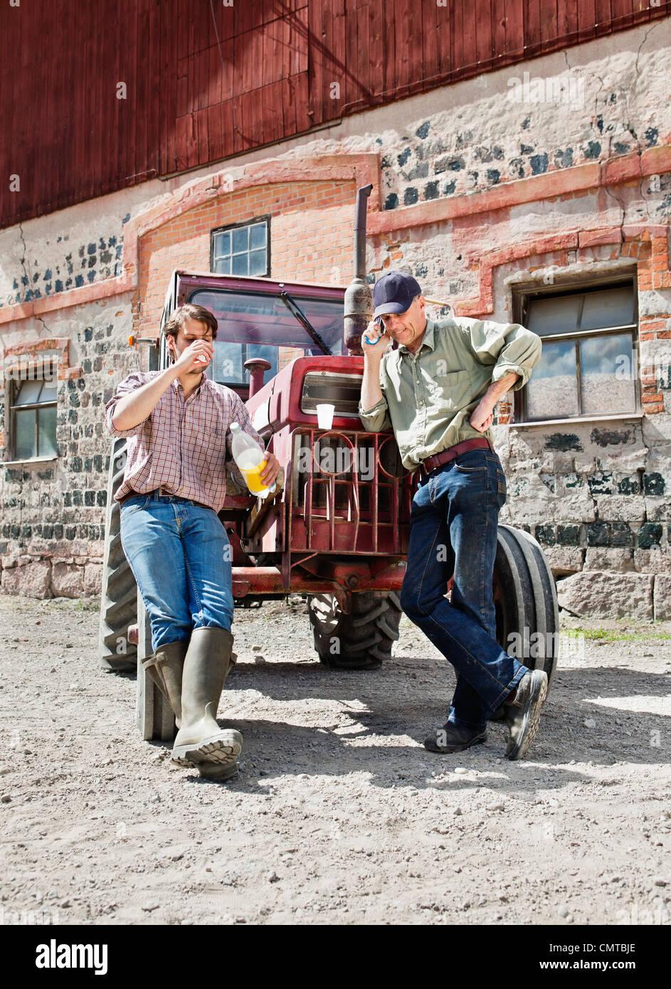 Männer stützte sich auf Traktor gegen Bauwerke Stockbild