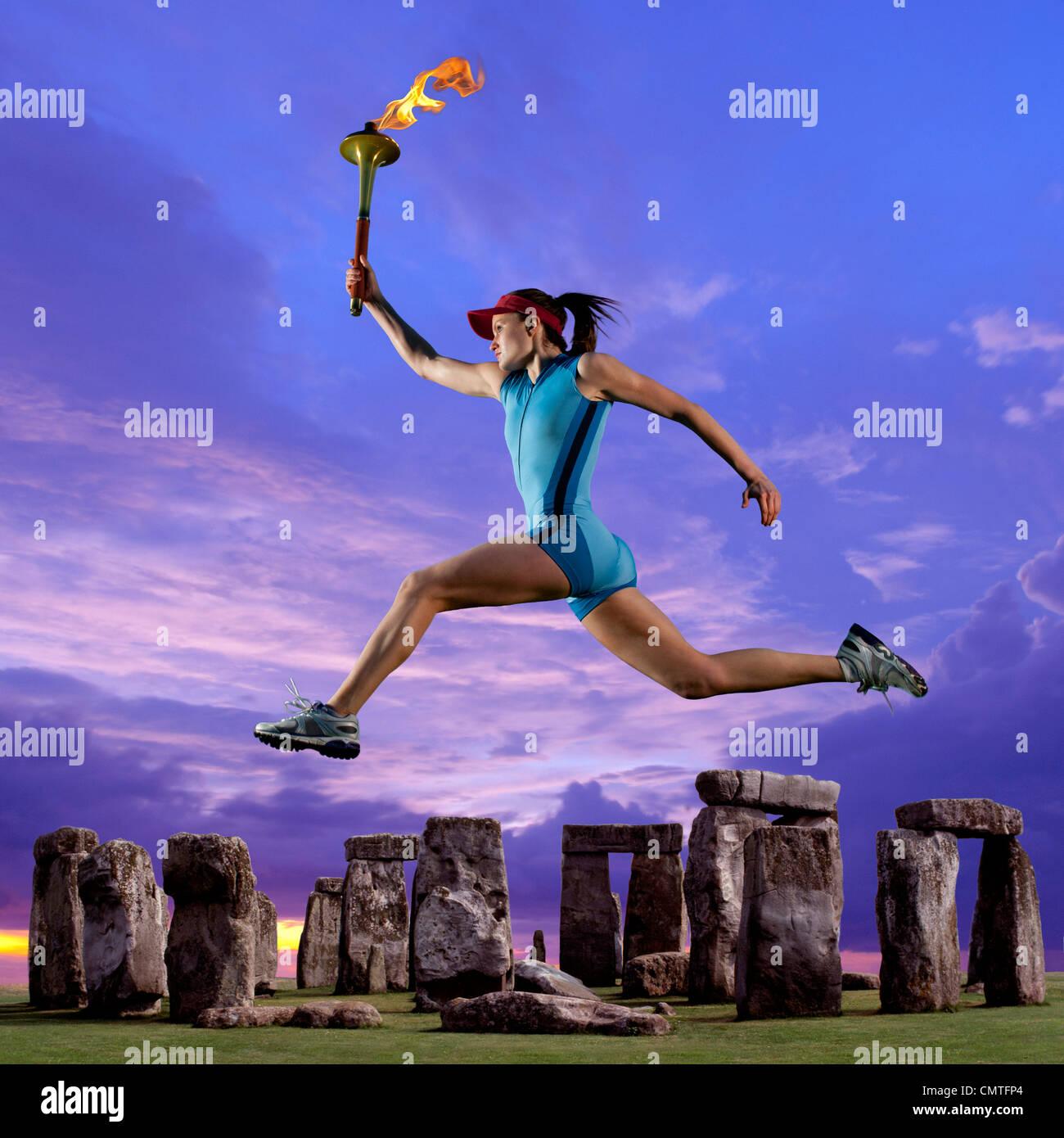 Athlet läuft mit der Olympischen Fackel in der Nähe von Stonehenge Stockfoto