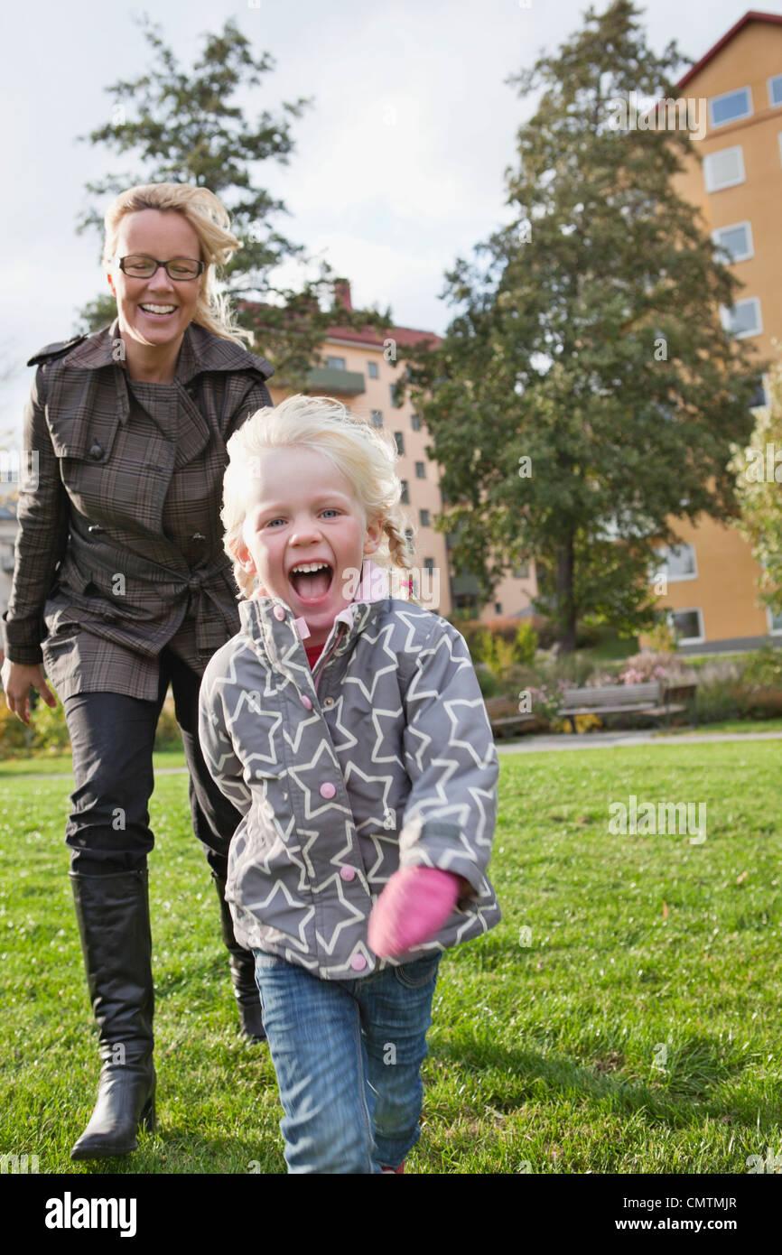 Frau und Tochter (2-3) in Bewegung gegen Bauwerke Stockbild