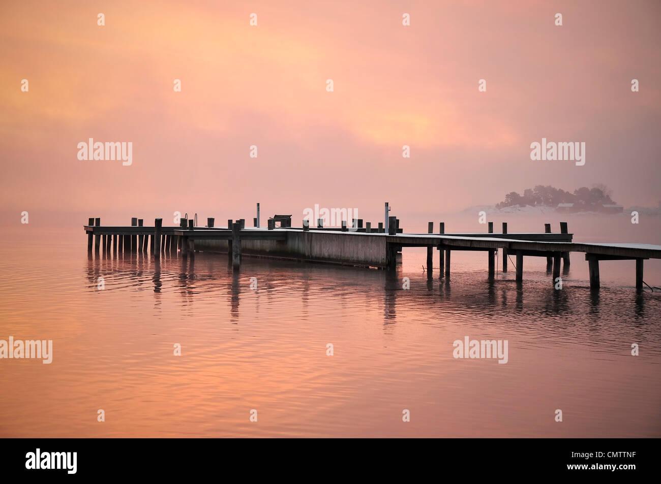 Steg, umgeben von Wasser in der Abenddämmerung Stockbild