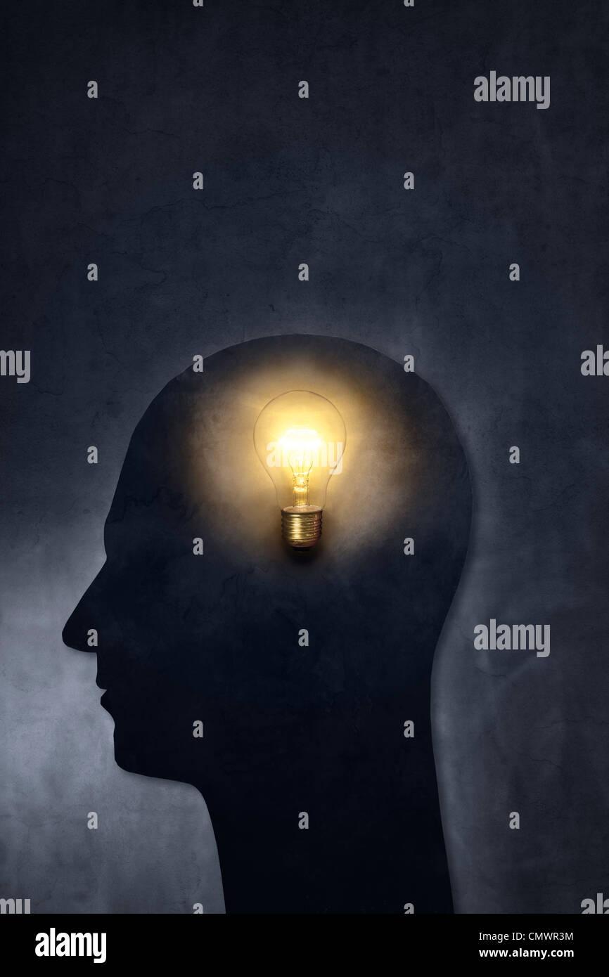 Künstlerische Silhouette eines Kopfes mit einer Glühbirne. Stockbild