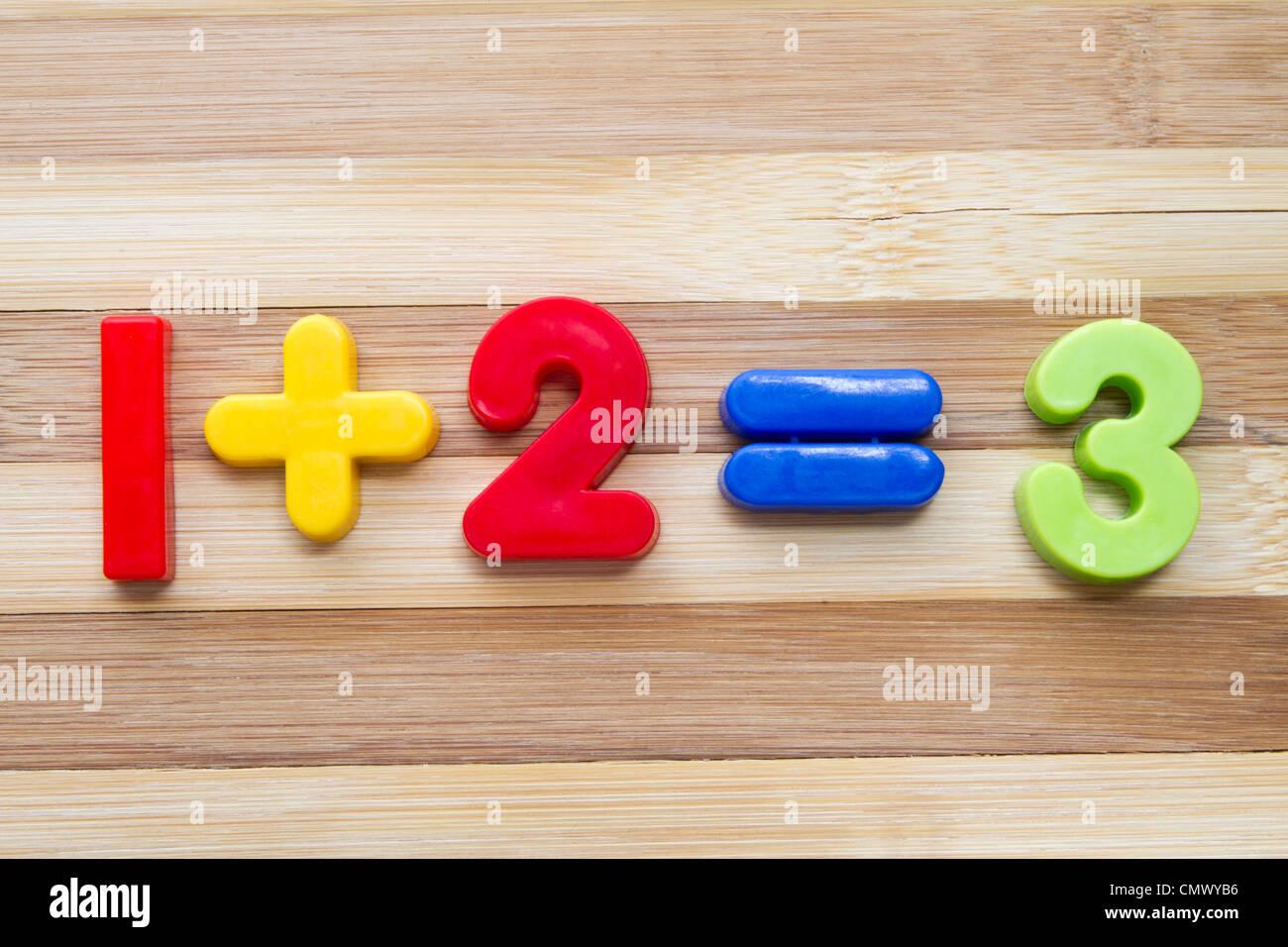 Mathe-Beispiel mit Zahlen Magneten auf Holz Hintergrund Stockbild