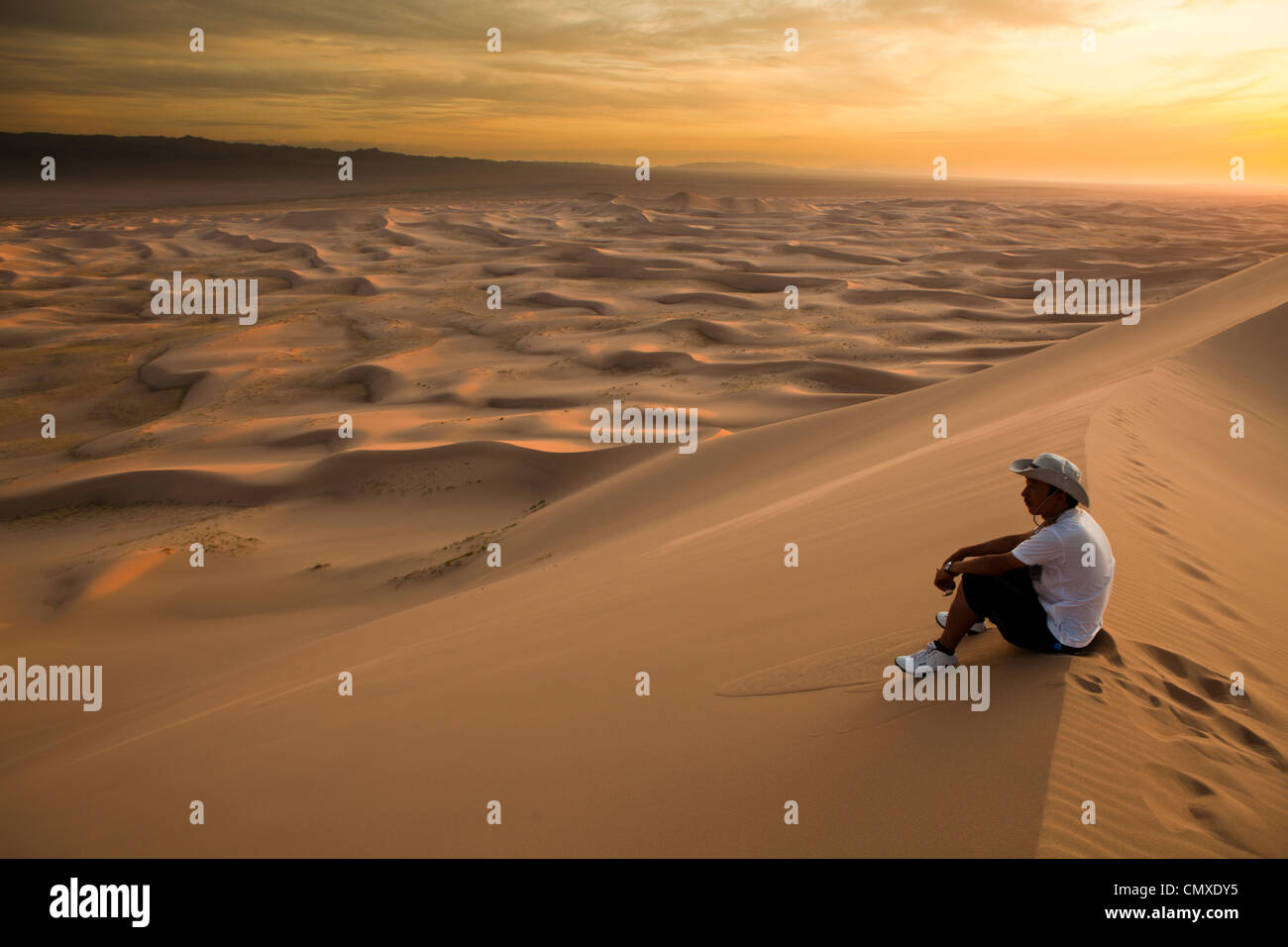 Der Mann sitzen auf Khongor Sanddünen, Wüste Gobi, Mongolei Stockbild