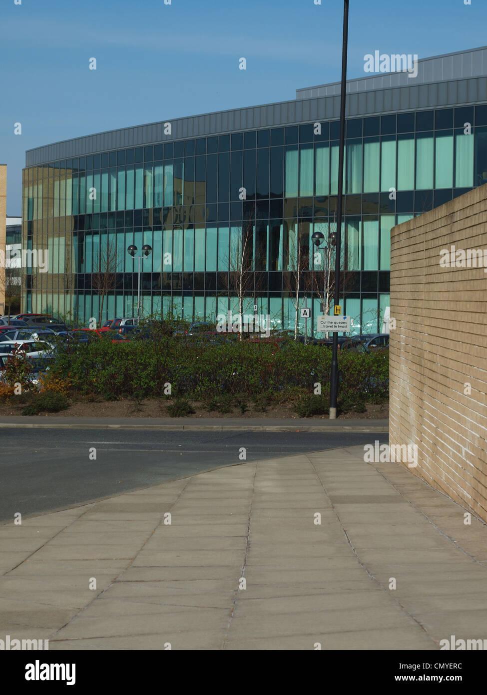 Ein Fußgängerweg flankiert von einer Mauer mit Klasse Plattenbauten im Hintergrund im Kobalt Business Stockbild