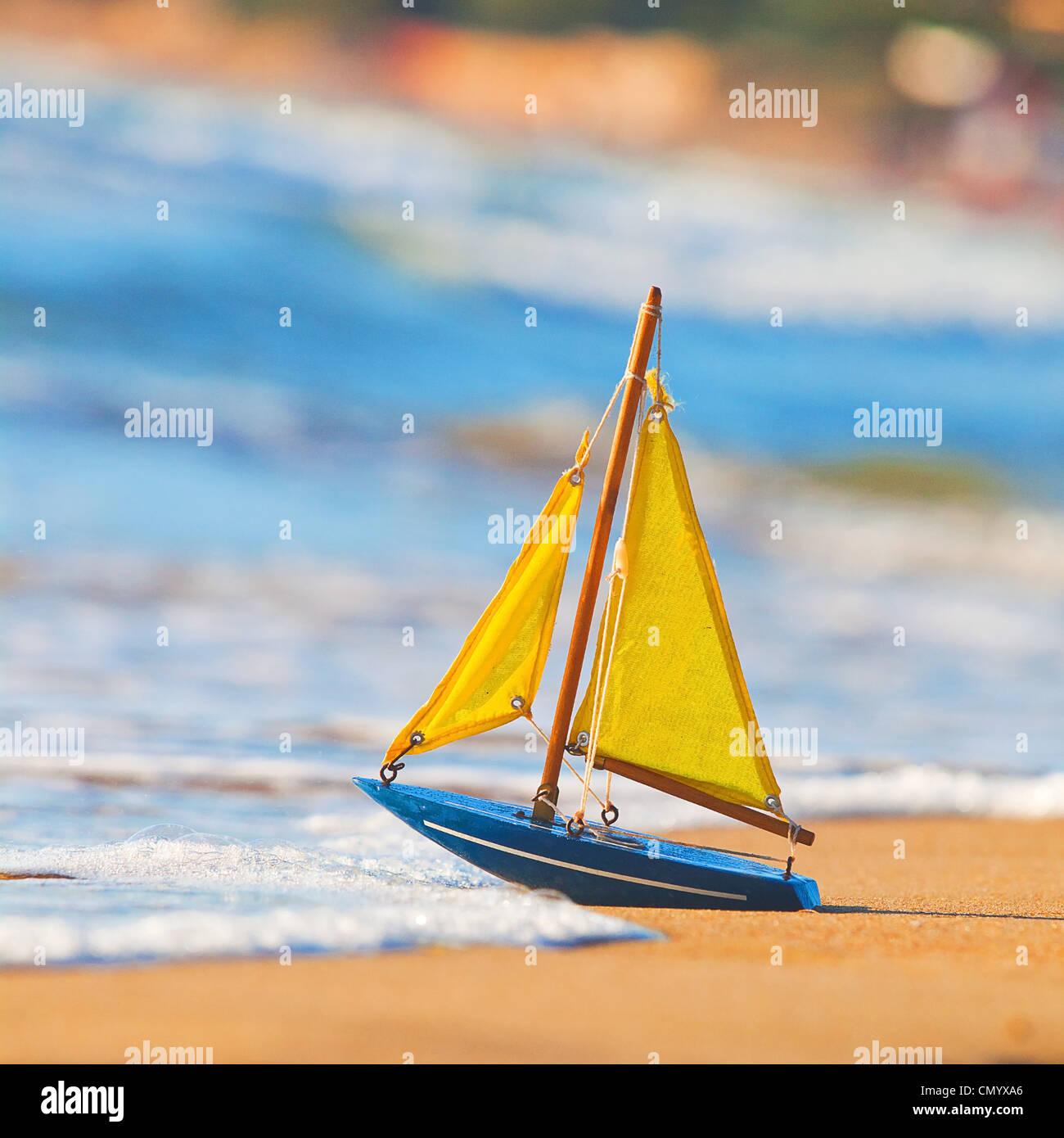 Das kleine Spielzeugboot steht am Sandstrand Stockbild