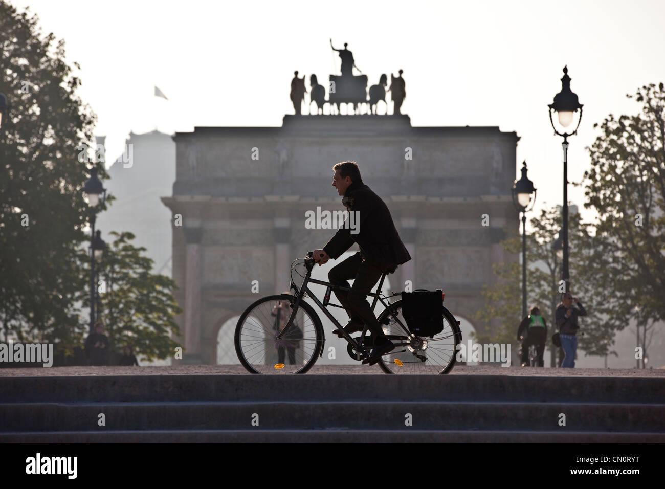 Ein am frühen Morgen Pendler Zyklen vorbei an der Arc de Triomphe du Carrousel in Jardin DesTuileries, Paris, Frankreich. Stockfoto