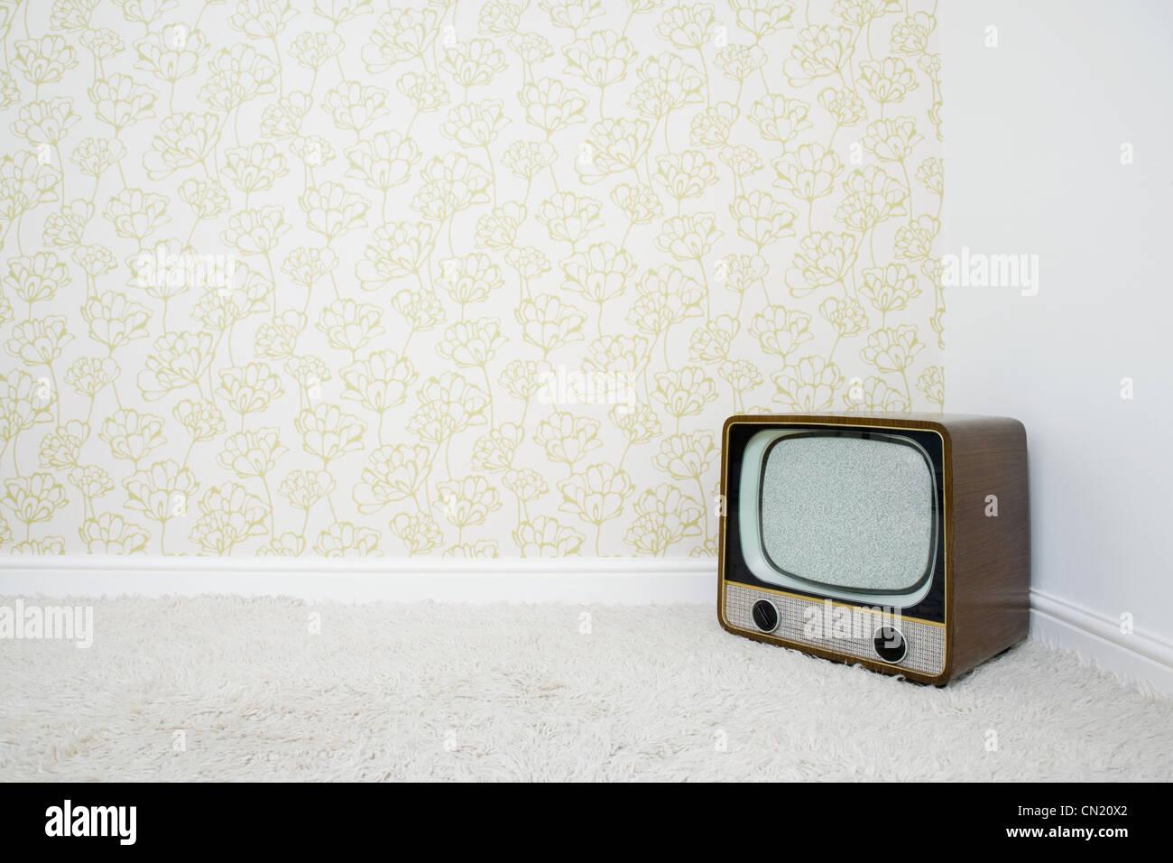 Retro-Fernseher in der Ecke des Raumes mit gemusterten Tapeten Stockbild