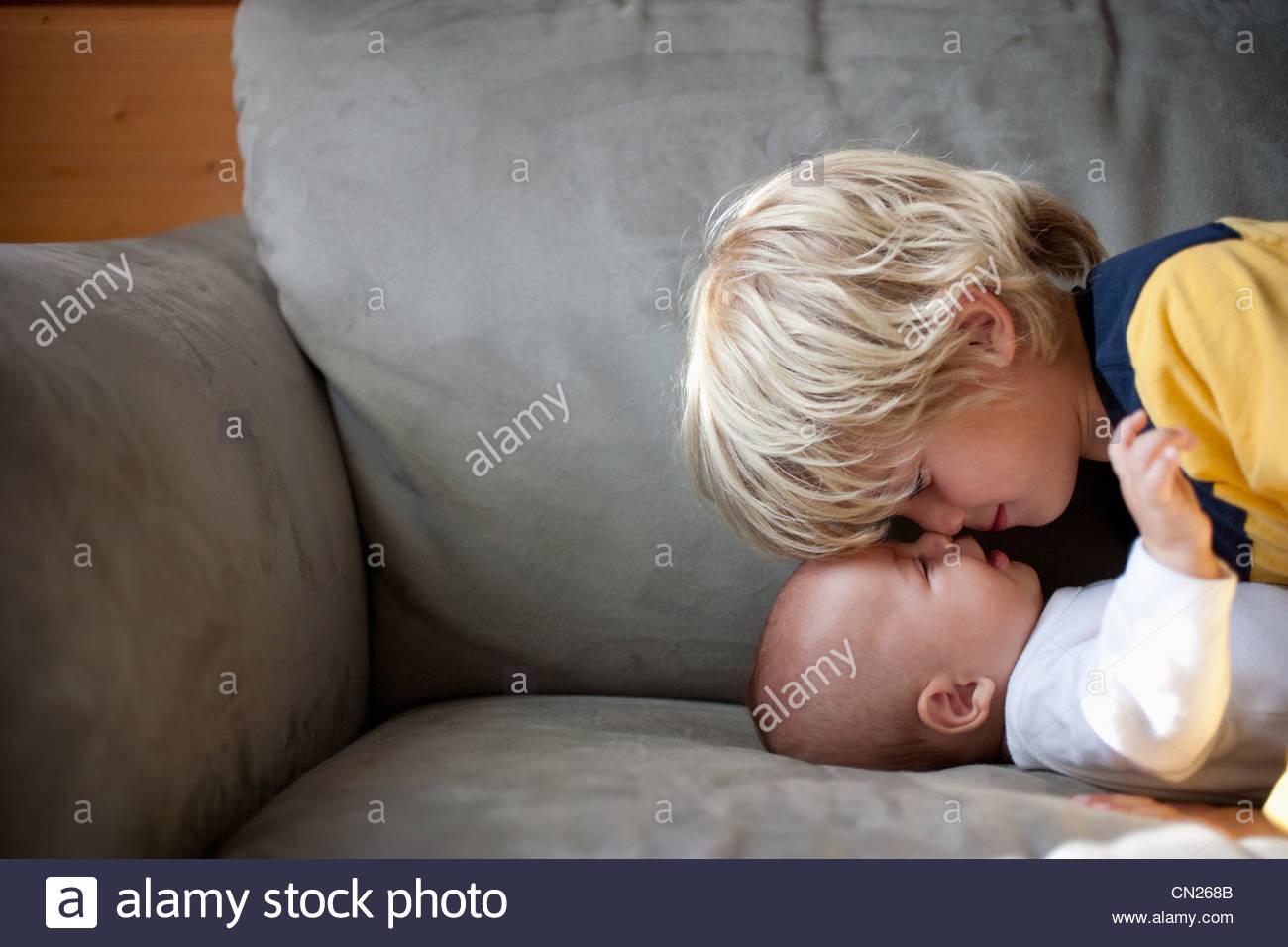 Junge Angesicht zu Angesicht mit kleinen Bruder auf sofa Stockbild