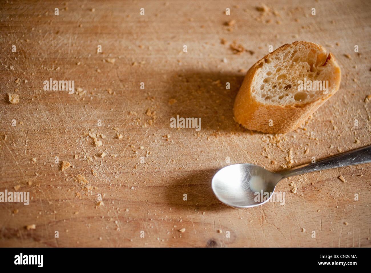 Teelöffel und Stück Brot auf Holzuntergrund Stockbild
