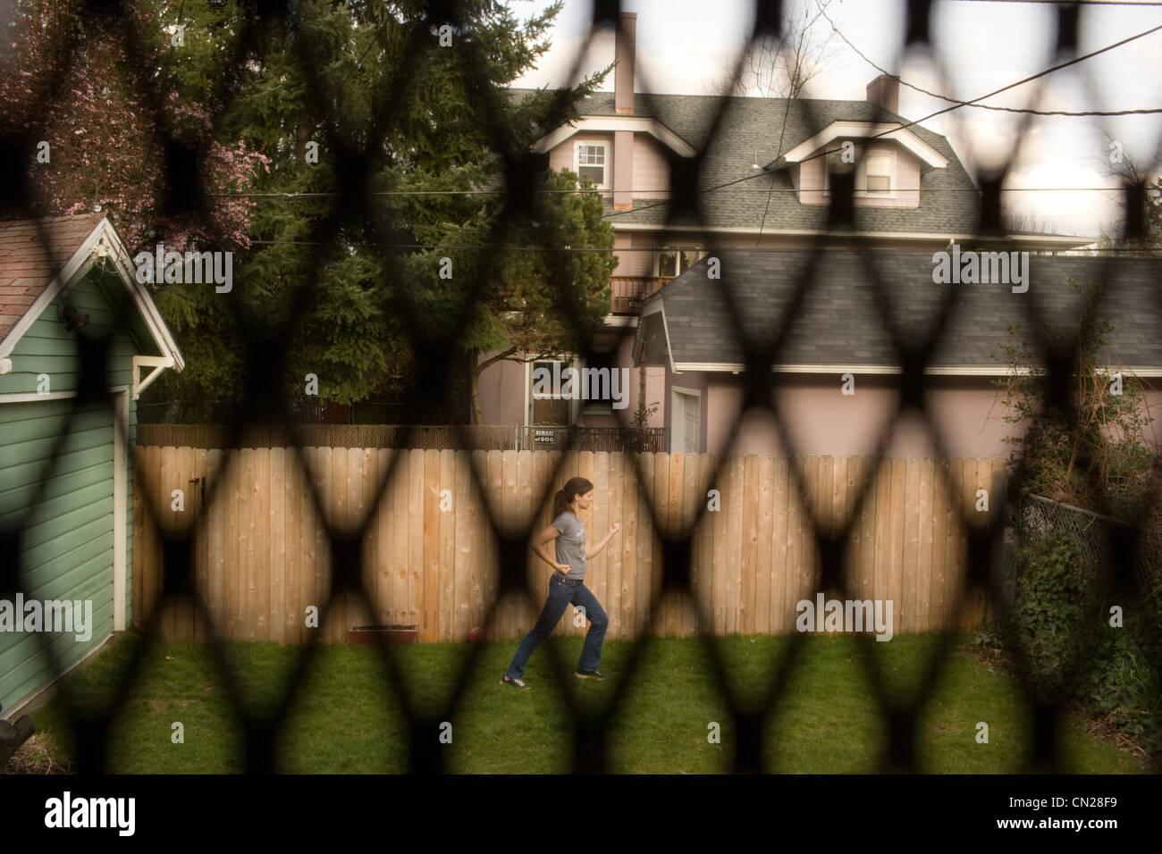 Blick durchs Fenster Frau Karate im Garten zu tun Stockbild