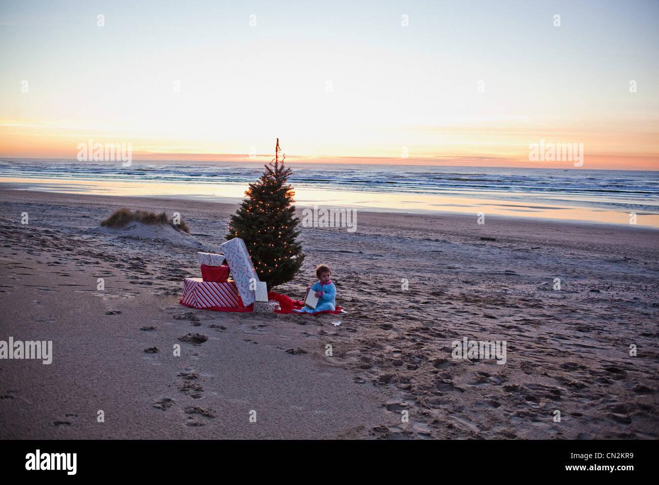 Junges Mädchen am Strand mit Weihnachtsbaum und Geschenke Stockfoto ...