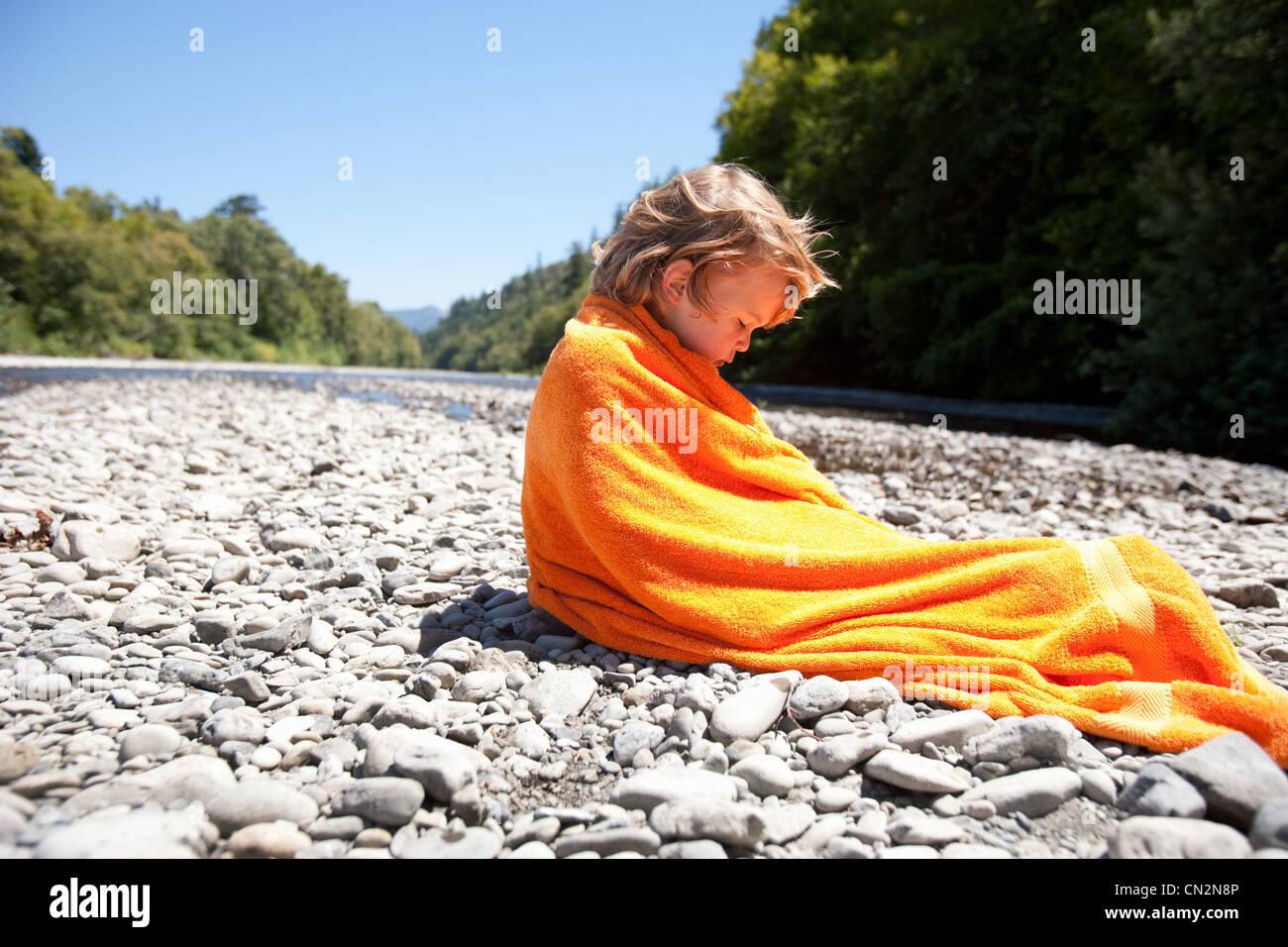 Junge gewickelt Handtuch sitzen auf Felsen Stockbild