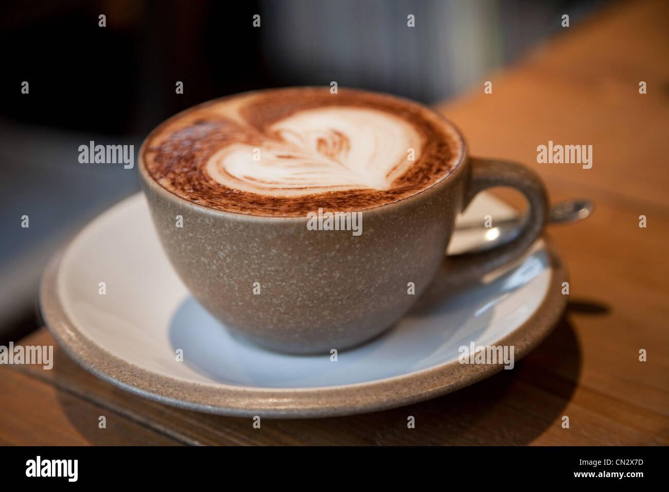 Cappuccino mit Herzform in Schaum Stockbild