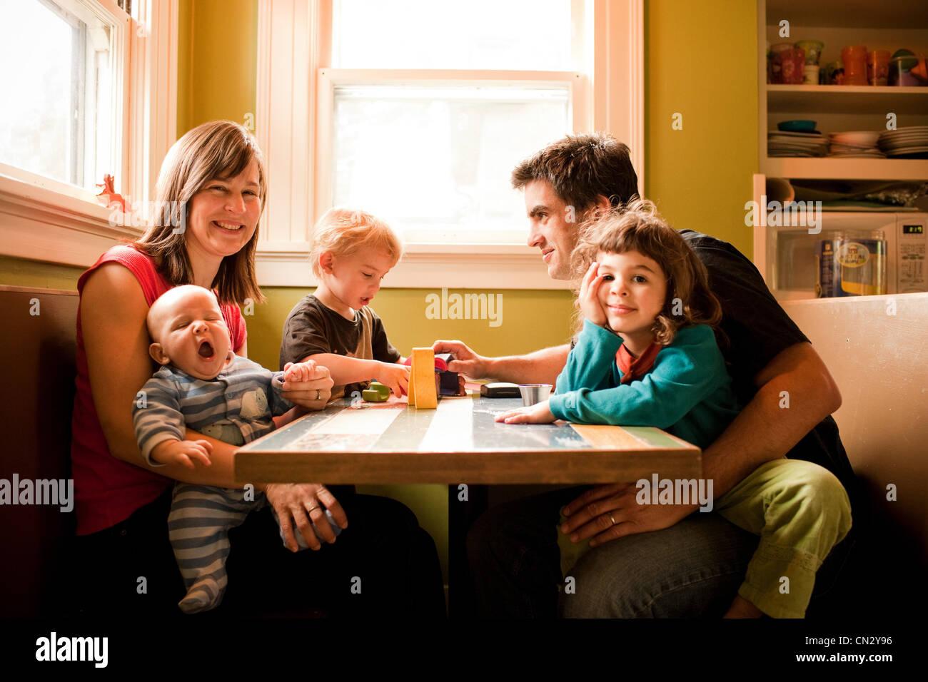 Familie sitzt am Küchentisch Stockfoto