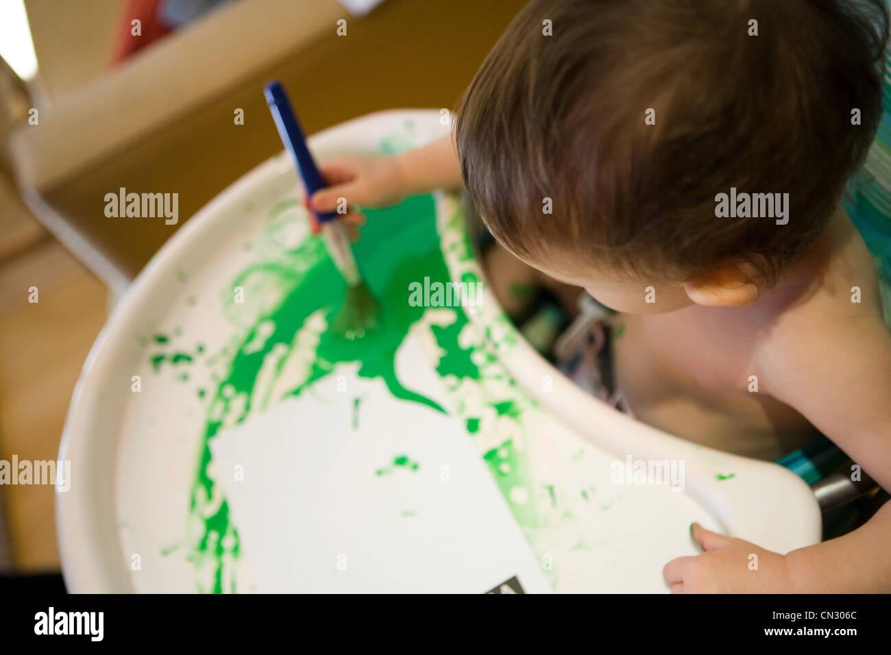 Baby Junge im Hochstuhl mit grüner Farbe Stockbild