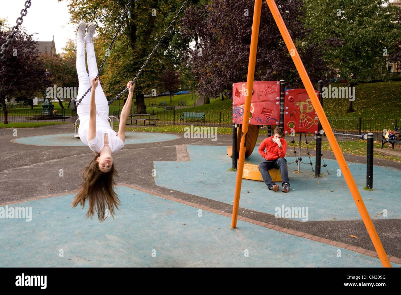 Teenager-Mädchen auf Schaukel Spielplatz, auf dem Kopf stehend Stockfoto