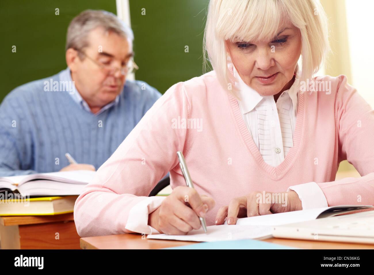 Zwei schwere Senioren tun eine Schreibaufgabe im Klassenzimmer Stockfoto