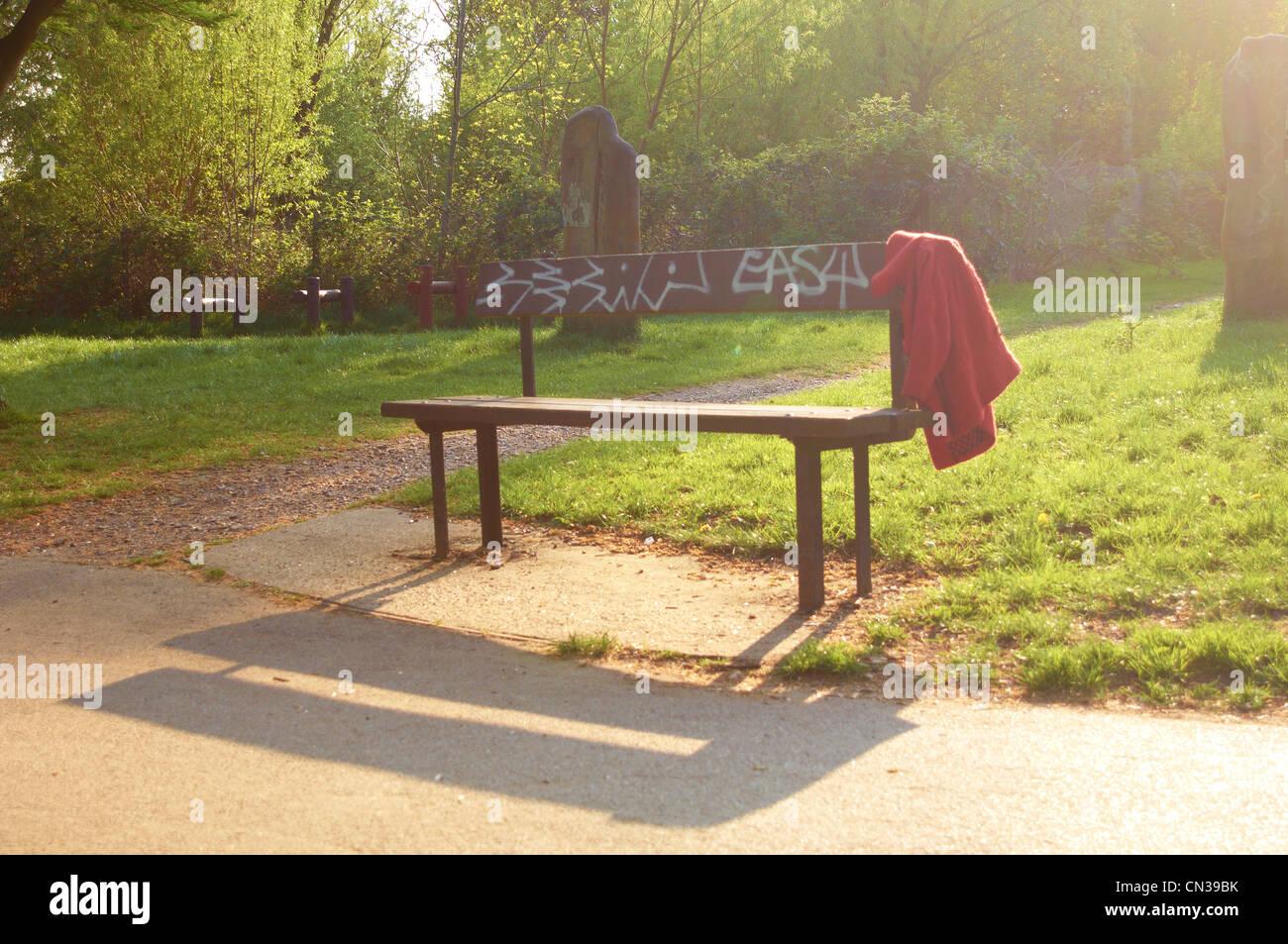 Verlorene Jacke auf einer Parkbank Stockbild