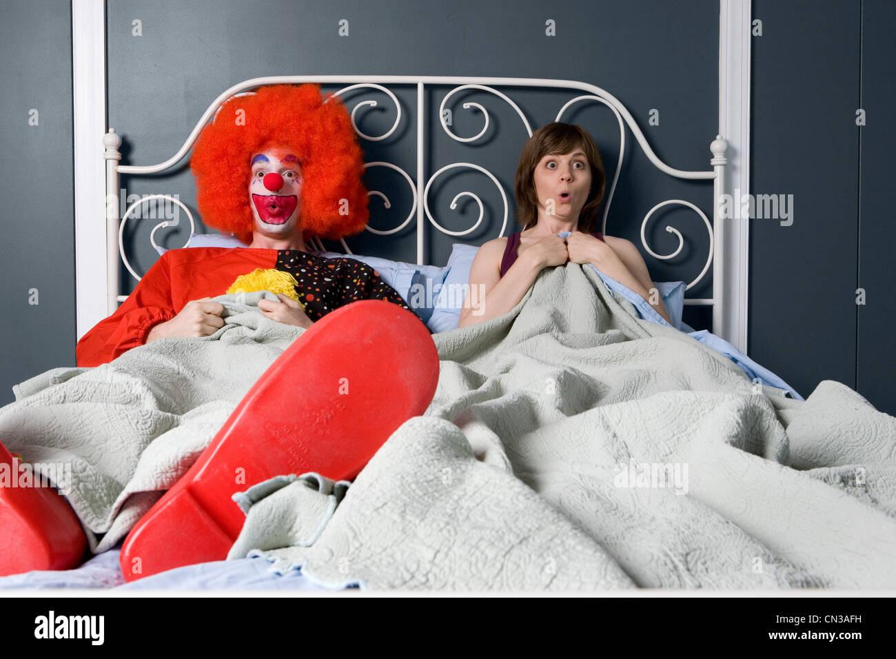 Clown und Frau finden sich zusammen im Bett überrascht Stockbild